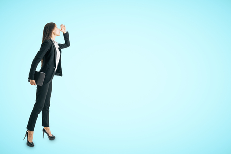 Attractive young white businesswoman looking into the distance on blue background with copy space. Research and future concept