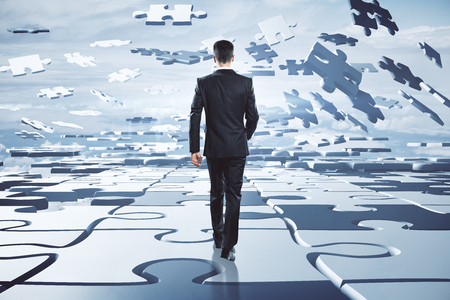 Solve and choice concept. Businessman on abstract cloudy sky background with jigsaw pieces. 3D Rendering Reklamní fotografie