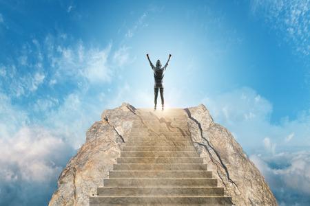 Jeune hacker monter les escaliers sur fond de ciel magnifique avec des nuages. Développement de carrière et concept de réussite