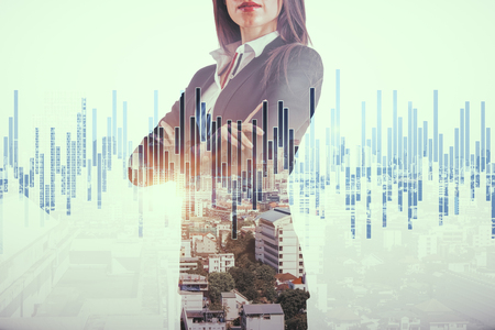 Attractive young european businesswoman standing on abstract city background with forex chart. Job and investment concept. Double exposure 스톡 콘텐츠