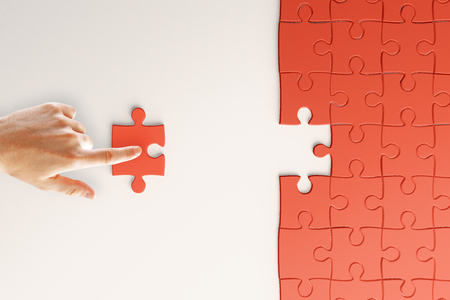 Creative background with hand fitting puzzle piece. Jigsaw and challenge concept. 3D Rendering