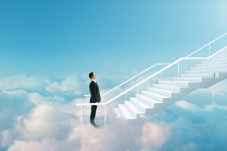 Young businessman climbing stairs on beautiful sky background with clouds. Career development and growth concept Stockfoto
