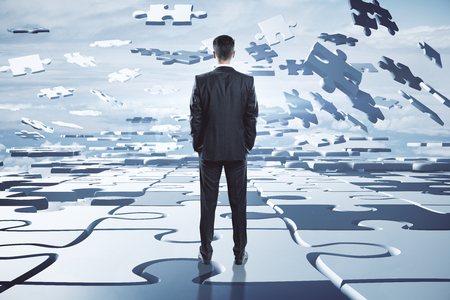 Teamwork and choice concept. Businessman on abstract cloudy sky background with jigsaw pieces. 3D Rendering