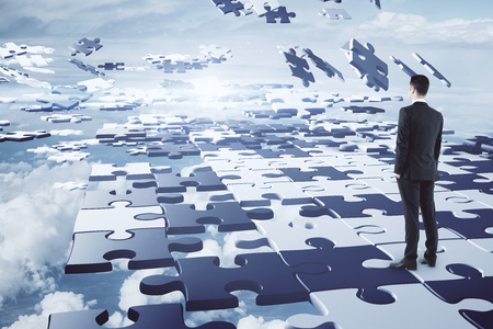 Challenge and freedom concept. Businessman on abstract cloudy sky background with jigsaw pieces. 3D Rendering