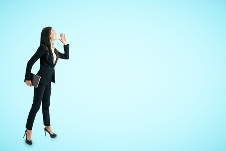 Attractive young caucasian businesswoman looking into the distance on blue background with copy space. Research and future concept