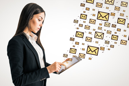 Side view of young caucasian businesswoman using tablet with abstract emails. E-mail marketing concept