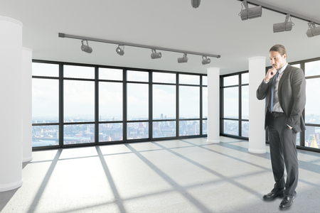 Handsome thoughtful young european businessman standing in modern empty office interior with city view and sunlight. 3D Rendering