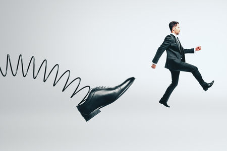 Abstract spring foot kicking businessman on white background. Supervision and fired concept Stock Photo