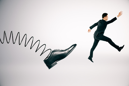 Abstract spring foot kicking businessman on white background. Supervision and discipline concept