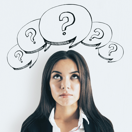 Portrait of attractive thoughtful young businesswoman with drawn question marks. Confusion and challenge concept