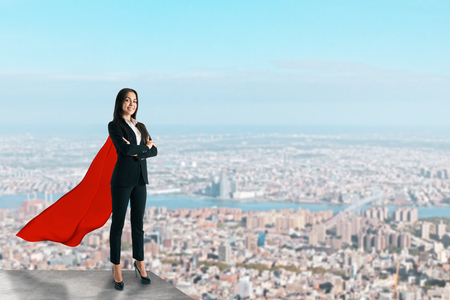 Beautiful young businesswoman with red hero cape on rooftop with blurry city view and daylight. Confidence and success concept