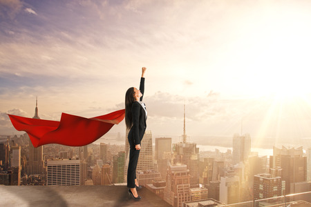 Beautiful young businesswoman with red hero cape on rooftop with blurry city view and daylight. Confidence and superhero concept