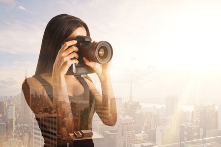 Young woman taking picture with professional camera on abstract city background. Double exposure Stock Photo