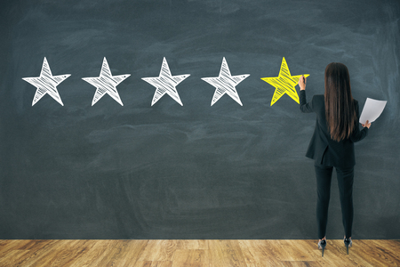 Back view of young businesswoman drawing stars on chalkboard wall. Rating and hospitality concept Stok Fotoğraf
