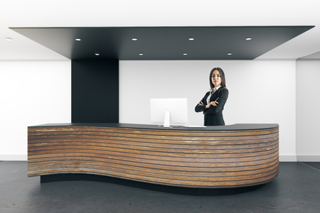 Attractive young european businesswoman standing at modern reception desk in office interior. 3D Rendering