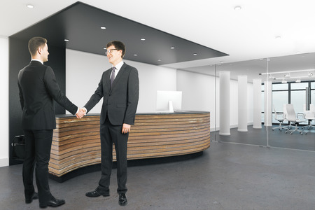 Two handsome european businessmen shaking hands in modern office interior. Teamwork and deal concept. 3D Rendering Stok Fotoğraf