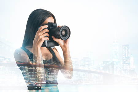 Young female taking picture with professional camera on abstract city background. Double exposure