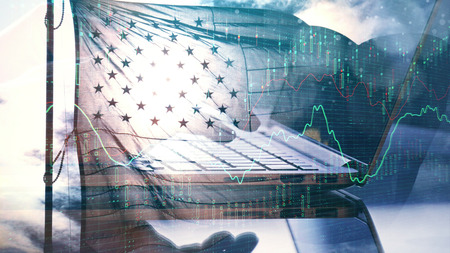 Hand using laptop with forex chart and american flag on sky background. Economy and trade concept. Double exposure