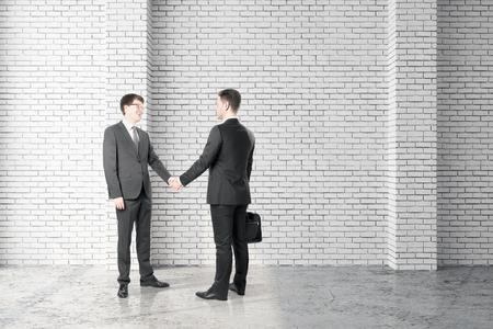 Attractive european businessmen shaking hands in modern brick interior. Teamwork and success concept. 3D Rendering Reklamní fotografie