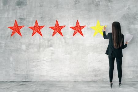Back view of young businesswoman drawing stars on concrete wall. Rating and exellence concept