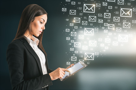 Side view of young european businesswoman using tablet with abstract emails. E-mail marketing concept