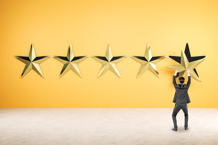 Back view of young businessman with five golden stars. Ranking and rating concept. 3D Rendering Stock Photo