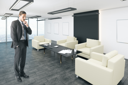 Thinking young european businessman standing in modern office lobby interior with posters. Mock up, 3D Rendering
