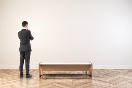 Przemyślany młody biznesmen stojący w białym wnętrzu hali wystawowej z pustą ścianą. Makieta, renderowanie 3D