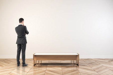 Thoughtful young businessman standing in white exhibition hall interior with empty wall. Mock up, 3D Rendering Stockfoto