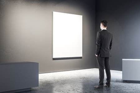 Young businessman looking at copy space in black gallery interior. Mock up, 3D Rendering 版權商用圖片