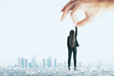 Teamwork and supervision concept. Hand holding businesswoman on sky and city background