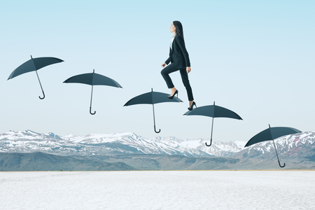 Side view of young businesswoman walking on umbrella ladder on winter mountain background. Financial security and ascend concept Stock Photo