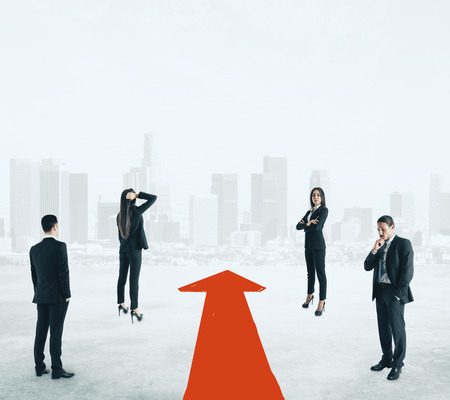 Attractive european businesspeople with red arrow on blurry white city background.  Teamwork and success concept 版權商用圖片
