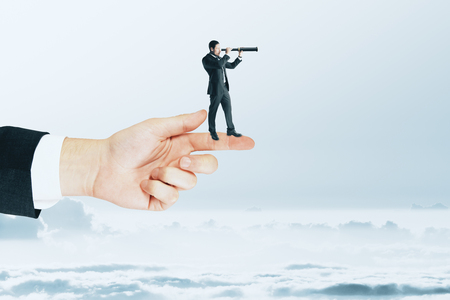 Research and future concept. Side view of young businessman using telescope white standing on finger. Sky background