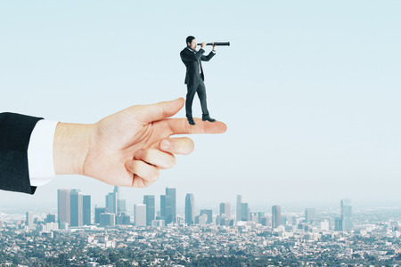 Research and search concept. Side view of young businessman using telescope white standing on finger. Sky background
