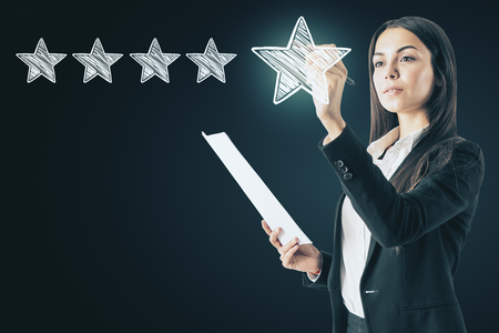Ranking and service concept. Attractive european woman drawing abstract star rating