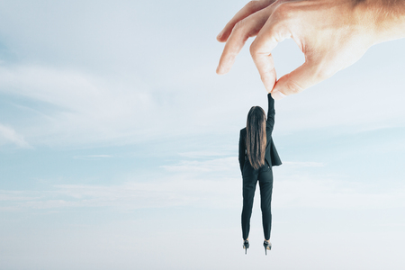 Teamwork and supervision concept. Hand holding businesswoman on sky background