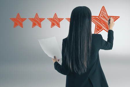 Ranking and satisfaction concept. Attractive european woman drawing abstract star rating Stock Photo