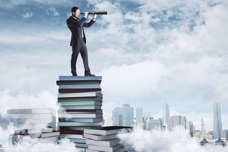 Curios businessman standing on book pile on cloudy sky and city background. Research and education concept