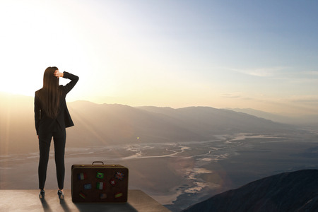 Back view of backlit woman standing on rooftop with luggage and beautiful landscape view. Travel and opportunity concept