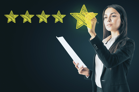 Ranking and exellence concept. Attractive european woman drawing abstract star rating