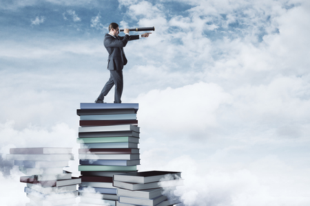 Curios businessman standing on book pile on cloudy sky and city background. Vision and education concept 스톡 콘텐츠