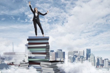 Happy businesswoman standing on book pile on cloudy sky and city background. Success and education concept Banco de Imagens