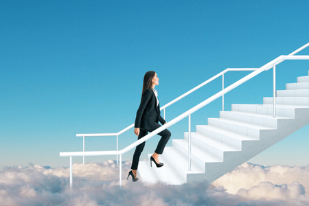 Side view of young businesswoman climbing heaven stairs on sky background with clouds. Success and growth concept