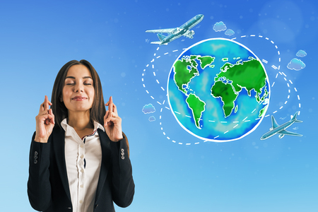 Attractive european businesswoman standing on blue background with travel globe with ariplane sketch and crossed fingers. Traveling concept Stockfoto