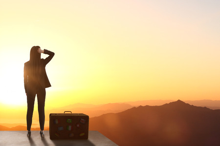 Back view of backlit woman standing on rooftop with luggage and beautiful landscape view. Vacation and opportunity concept
