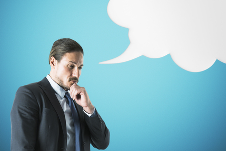 Attractive young businessman with thoughtspeech cloud. Speech and freedom concept
