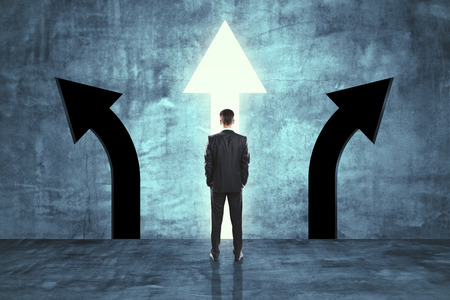 Back view of young businessman in concrete room with three arrows. Different direction and choice concept Banco de Imagens