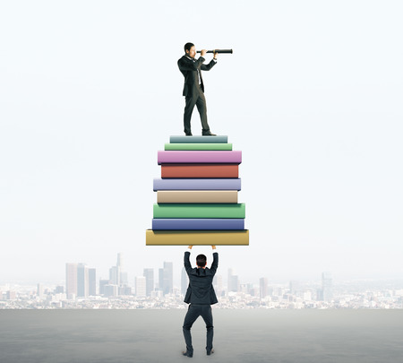 Businessman holding book stack with colleague looking into the distance with telescope on blurry city background. Knowledge and research concept Stock Photo