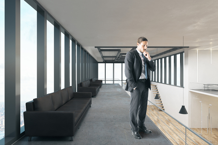 Thoughtful businessman standing in modern office interior with panoramic sky view. 3D Rendering